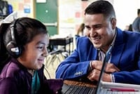Teacher smiling at student on laptop